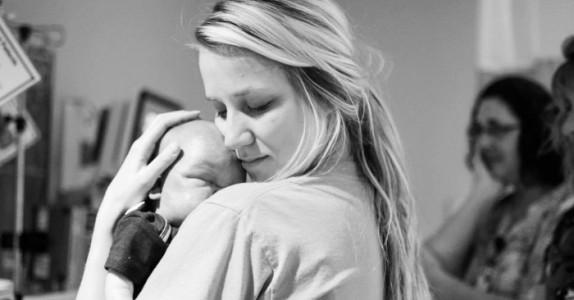 Sykepleieren holder den døde babyen. Men sannheten bak bildet rører tusenvis til tårer.