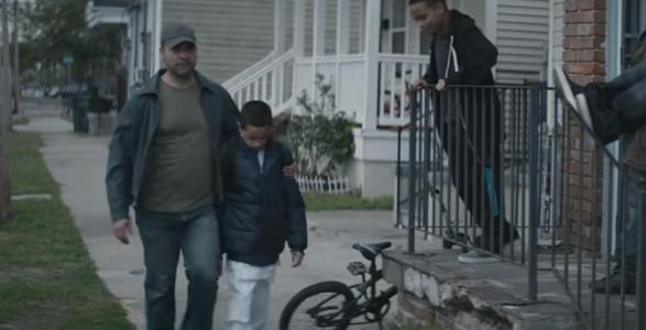 Faren beskytter sønnen fra mobberne. Men se hva gutten har under den blå jakken…