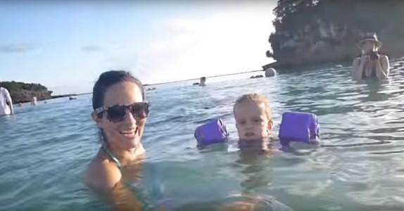 Mor poserer med ungen på stranden. Men følg NØYE med bak dem… Utrolig!
