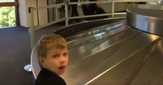 Gutten står og venter på bagasjen sin på flyplassen. Men se hva som plutselig dukker opp!