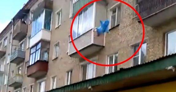 Alle på fortauet følger spent med. Så kaster pappaen babyen fra 5. etasje!
