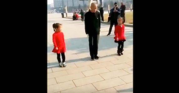 Den gamle mannen stiller seg mellom de to jentene i rødt. Det neste han gjør får alle til å juble!