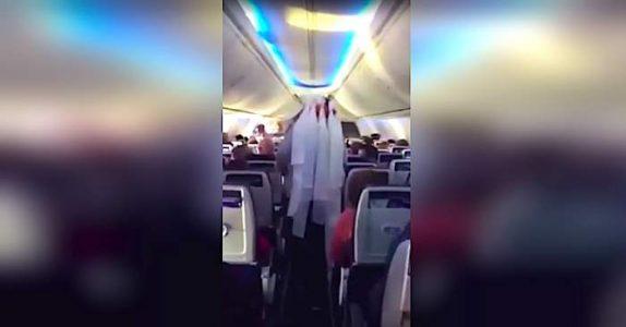 Kvinnen går langs midtgangen på flyet. Da oppdager de andre passasjerene at hun har noe på HODET!